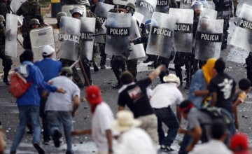 Supporters of Honduras' President Manuel Zelaya clash with police near the presidential residence in Tegucigalpa June 29, 2009. Honduras came under pressure on Monday to reinstate ousted Zelaya as many Latin American leaders agreed to withdraw envoys, Washington said the ouster was illegal and protesters took to the streets.   REUTERS/Edgard Garrido (HONDURAS POLITICS CONFLICT IMAGES OF THE DAY)