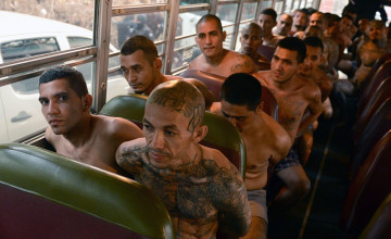 Gang members are seen inside a bus as they are transferred to a high-security prison on April 24, 2015 in Izalco, El Salvador. About 400 feared gang members were transferred under heavy guard to a high-security prison in El Salvador in an attempt Friday to choke the criminal networks behind an upsurge in already sky-high violence.  AFP PHOTO / Marvin RECINOS