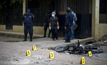 Forensic personnel work on the scene where an alleged gang member was killed by the police after a shooting at El Pedregal neighborhood in Tegucigalpa, on November 21, 2013. Honduras, considered the world's most violent country with a murder rate of 85,5 per 10,000 of population, will hold general elections next November 24th. AFP PHOTO/ Jose CABEZAS        (Photo credit should read Jose CABEZAS/AFP/Getty Images)