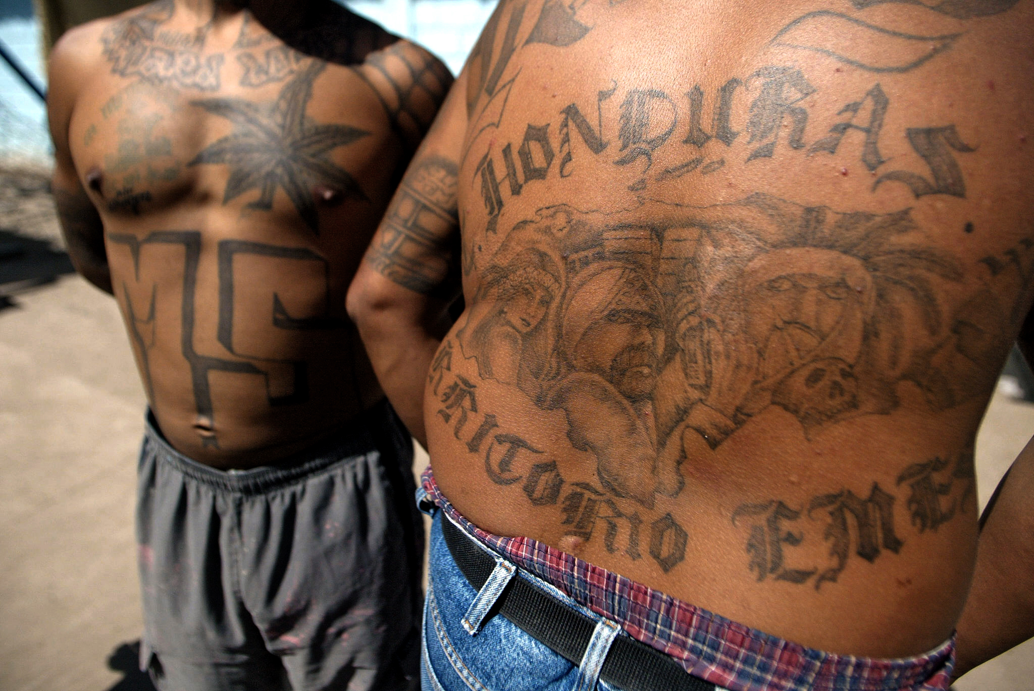 """Two unidentified members of the Mara Salvatrucha """"MS-13"""" (juvenile gang) show their tatoos in the unit where they are kept imprisioned in the National Penitentiary in Tamara, 30km north of Tegucigalpa, 01 February 2006. AFP PHOTO/Elmer MARTINEZ"""