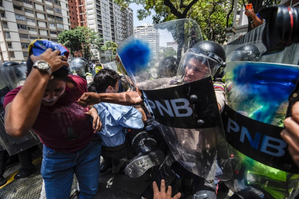 Venezuela's opposition activists scuffle with riot police during a protest against Nicolas Maduro's government in Caracas on April 4, 2017.  Protesters clashed with police in Venezuela Tuesday as the opposition mobilized against moves to tighten President Nicolas Maduro's grip on power. Protesters hurled stones at riot police who fired tear gas as they blocked the demonstrators from advancing through central Caracas, where pro-government activists were also planning to march. / AFP PHOTO / JUAN BARRETO        (Photo credit should read JUAN BARRETO/AFP/Getty Images)