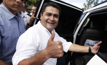 Juan Hernandez (R), presidential candidate for the ruling National Party, gestures while boarding a vehicle in Tegucigalpa November 24, 2013. Hondurans voted for a new president on Sunday, choosing between a tough militarized response to drug gang violence fueling the world's highest murder rate, and a shift to the left that could revive thepolitical career of deposed leader Manuel Zelaya. A photo-finish finale is expected in a race that pits the ruling National Party's candidate, conservative Juan Hernandez, the head of Congress viewed as Honduras' most powerful politician, against Zelaya's wife, Xiomara Castro. REUTERS/Jorge Cabrera (HONDURAS - Tags: ELECTIONS POLITICS)