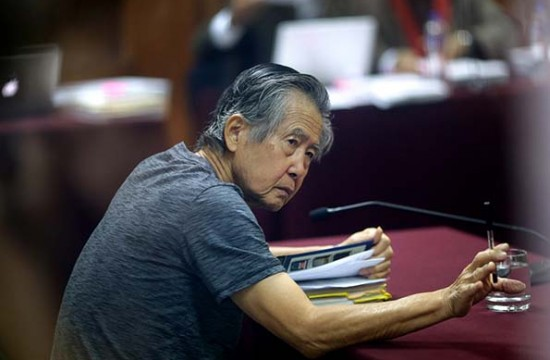 FILE - In this April 23, 2014 file photo, jailed former Peruvian President Alberto Fujimori, photographed through a glass window, attends his trial at a police base on the outskirts of Lima, Peru. The man who stands most to benefit from Pedro Pablo Kuczynski's presidential victory in Peru may be her defeated rival's father: imprisoned ex-President Alberto Fujimori. (AP Photo/Martin Mejia, File)
