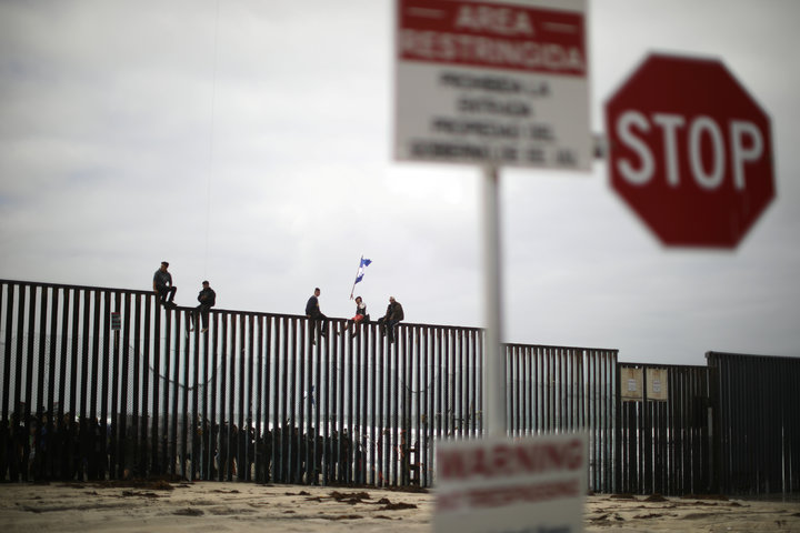 Members of a migrant caravan from Central America and their supporters sit on the top of the U.S.-Mexico border wall at Border Field State Park before making an asylum request, in San Diego, California, U.S. April 29, 2018. REUTERS/Lucy Nicholson